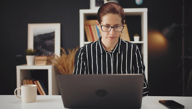 テーブル、e-workに座って自宅からラップトップに取り組んでいる中年の真面目な女性の正面図