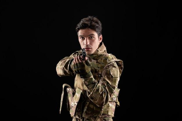 검은 벽에 총을 든 제복을 입은 군인의 전면 모습