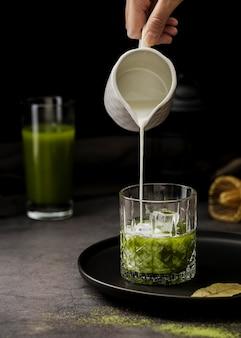 Вид спереди молока, наливаемого в матовый чайный стакан с кубиками льда