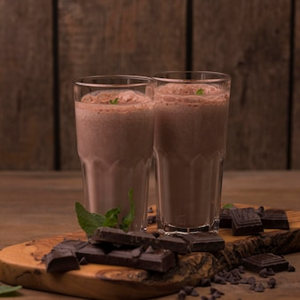 Вид спереди стаканов для молочного коктейля с шоколадом и мятой