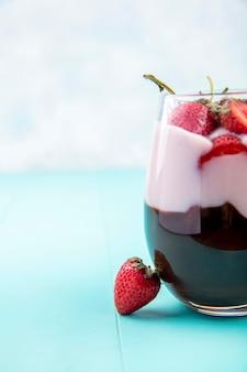 Вид спереди молочный коктейль с шоколадом и клубникой на стакан на синем столе на белой поверхности