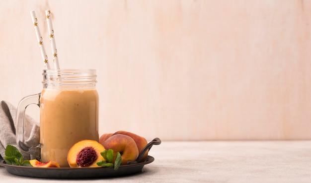 Вид спереди молочного коктейля с персиками и копией пространства