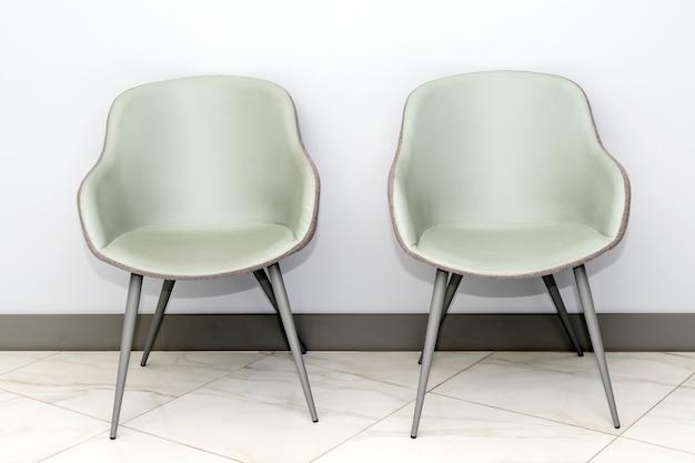 최소한의 스타일 대기실 내부에 회색 벽에 현대적이고 간단한 의자의 전면 뷰. 텍스트 복사 공간 의사의 사무실 대기실 의자