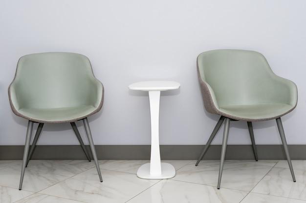 최소한의 스타일, 대기실 인테리어의 회색 벽에 흰색 테이블이있는 현대적이고 간단한 의자의 전면보기. 텍스트 복사 공간 의사의 사무실 대기실 의자