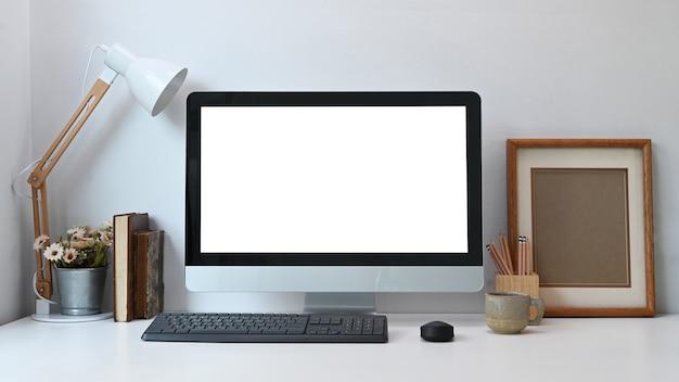 Вид спереди современного рабочего места с пустым компьютером и различными офисными инструментами на белом столе.