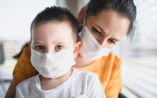 집에서 안면 마스크를 쓴 엄마와 어린 아이의 앞모습