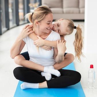 Вид спереди матери занимаются йогой с дочерью дома