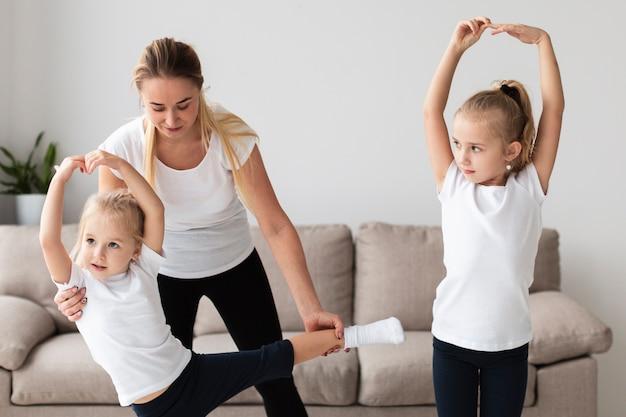 娘が自宅でヨガの練習を助ける母親の正面図