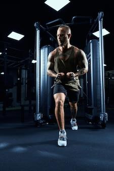 Вид спереди мускулистого культуриста в спортивной одежде, делающего кроссовер с низким кабелем.