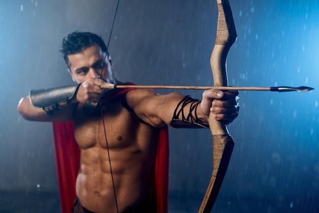 雨が降っている間、矢で弓から撃つ、赤いマントを身に着けている筋肉の成熟したスパルタンの正面図。悪天候でポーズをとる歴史的な衣装で濡れたハンサムな男の腕の中で武器の選択的な焦点。