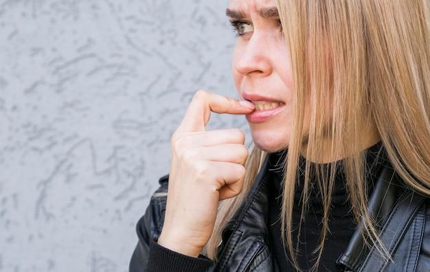 Вид спереди на гвоздь, кусающий вредную привычку
