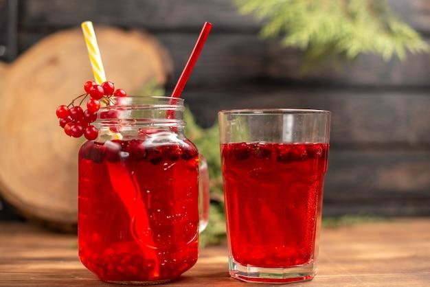 チューブ付きのボトルと木製のテーブルのガラスに入った天然の有機新鮮なカシス ジュースの正面図