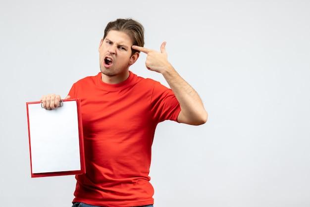 白い背景の上のドキュメントを保持している赤いブラウスで神経質な怒っている感情的な若い男の正面図