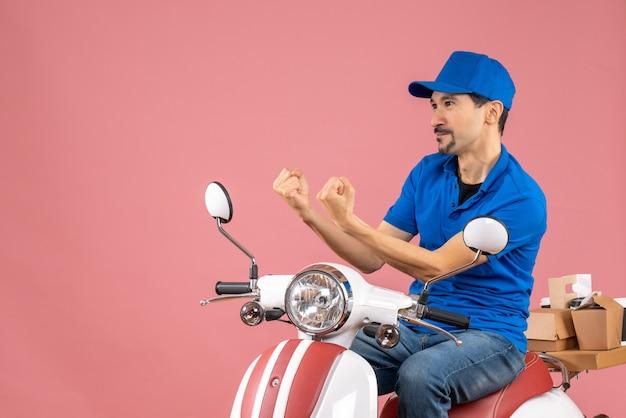 Вид спереди нервного курьера в шляпе, сидящего на скутере на пастельном персиковом фоне