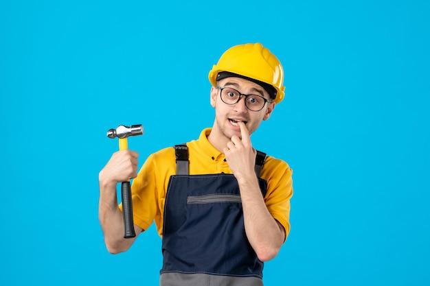 Вид спереди нервного мужчины-строителя в форме с молотком на синем