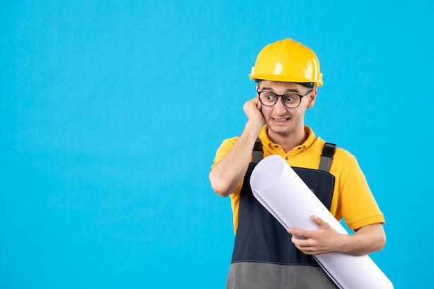Вид спереди нервного мужчины-строителя в желтой форме и шлеме с планом на синем