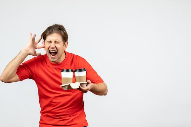 紙コップでコーヒーを保持し、白い背景の上の彼の耳の1つを閉じる赤いブラウスで神経質な若い男の正面図