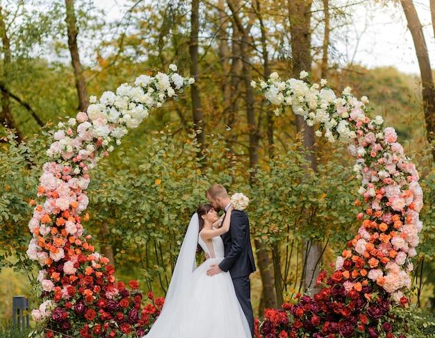 꽃 아치 배경 공원에서 결혼식에서 포옹하는 신혼 부부의 전면보기