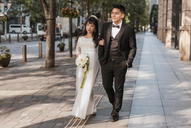 거리를 걷는 꽃의 부케와 함께 신혼 부부의 전면보기