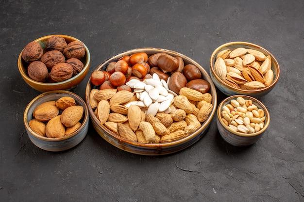 濃い灰色の表面上のナッツ組成ピーナッツおよび他のナッツの正面図