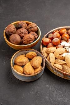 灰色の表面上のナッツ組成ピーナッツおよび他のナッツの正面図