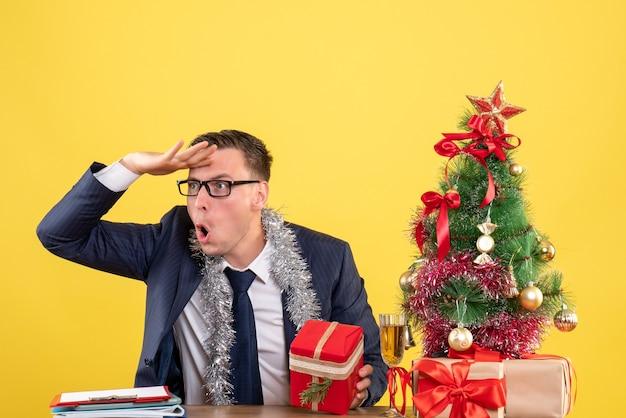 Вид спереди наблюдающего молодого человека в очках, сидящего за столом возле рождественской елки и подарков на желтом