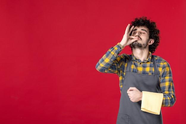 孤立した赤い壁の上に立って完璧なジェスチャーを作るタオルを保持している巻き毛を持つ若い笑顔の男性サーバーの正面図