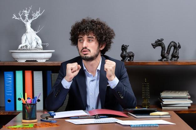 オフィスの机に座っているサラリーマンの正面図