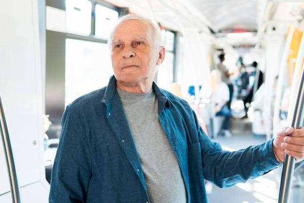 Вид спереди старика в общественном транспорте