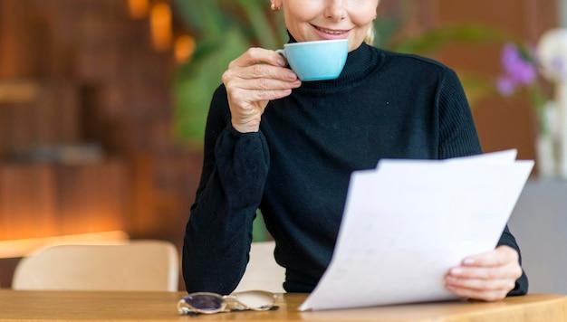 Вид спереди пожилой деловой женщины, читающей документы за чашкой кофе