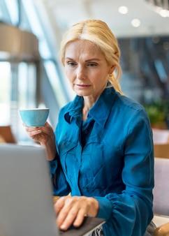Вид спереди пожилой деловой женщины, работающей на ноутбуке и держащей чашку кофе