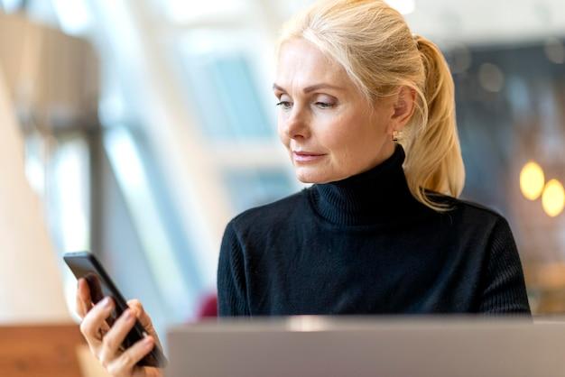 ラップトップに取り組んでいるとスマートフォンを見て古いビジネス女性の正面図