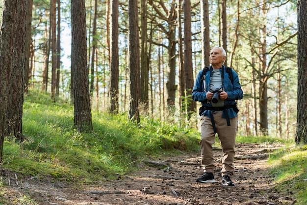 バックパックで屋外の自然を探索する年上の男の正面図
