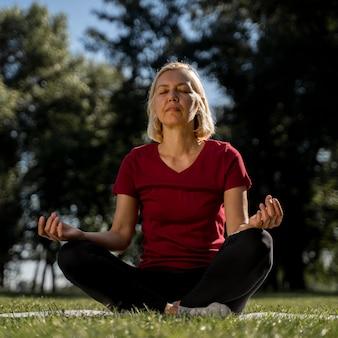 Вид спереди пожилой женщины в позе лотоса на открытом воздухе во время йоги
