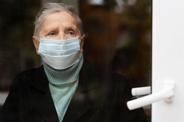 Вид спереди пожилой женщины с медицинской маской за стеклянной дверью