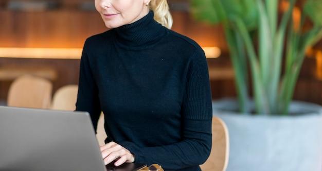 Вид спереди пожилой женщины, работающей на ноутбуке