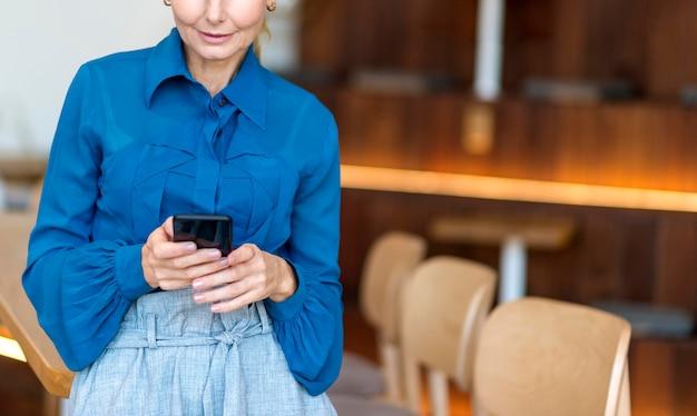 Вид спереди пожилой женщины, работающей на смартфоне во время отсутствия