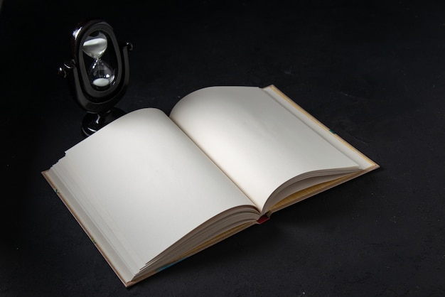 Вид спереди открытой книги с песочными часами на черном
