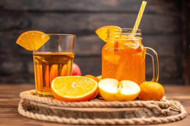 まな板の上にチューブと果物を添えた、ボトルとグラスに入った有機フレッシュ ジュースの正面図