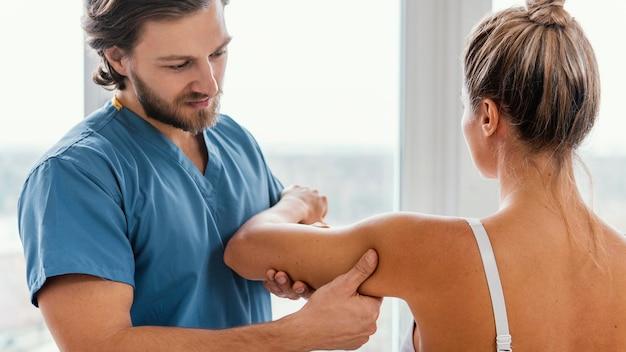 여성 환자의 어깨 움직임을 확인하는 정골 치료사의 전면보기