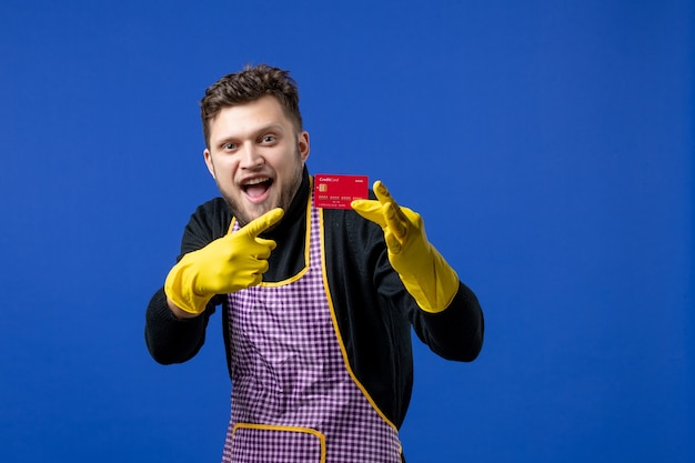 青い壁のカードを指して大喜びの若い男の正面図