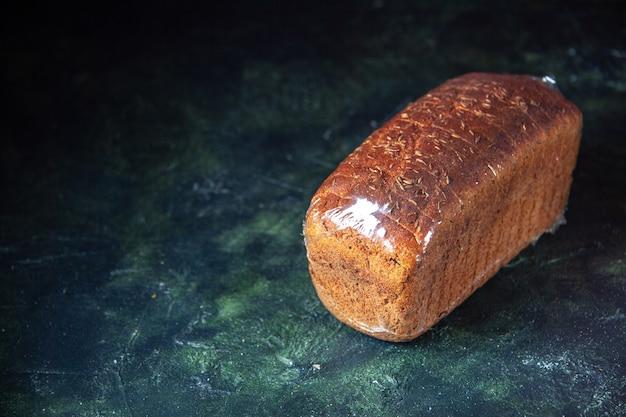 Вид спереди упакованного черного хлеба слева на синем и черном фоне смешанных цветов со свободным пространством