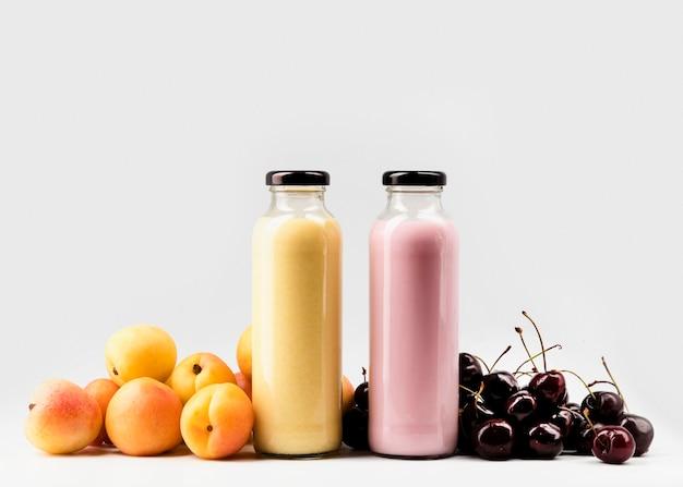 Вид спереди на бутылки персикового и вишневого сока
