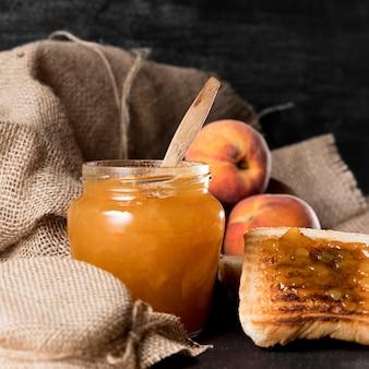 Вид спереди персикового мармелада в банке с хлебом