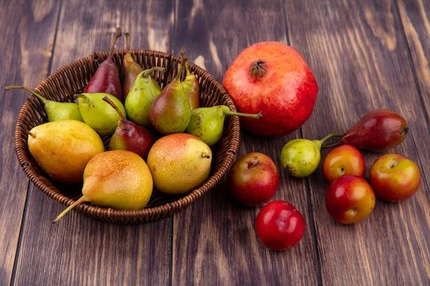 Вид спереди персики в корзине с гранатово-персиковым сливы на деревянной поверхности