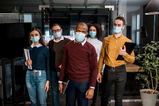 회의를 위해 사무실에서 의료 마스크를 가진 사람들의 전면보기