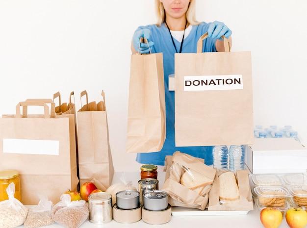 Вид спереди человека, раздающего сумки для пожертвований