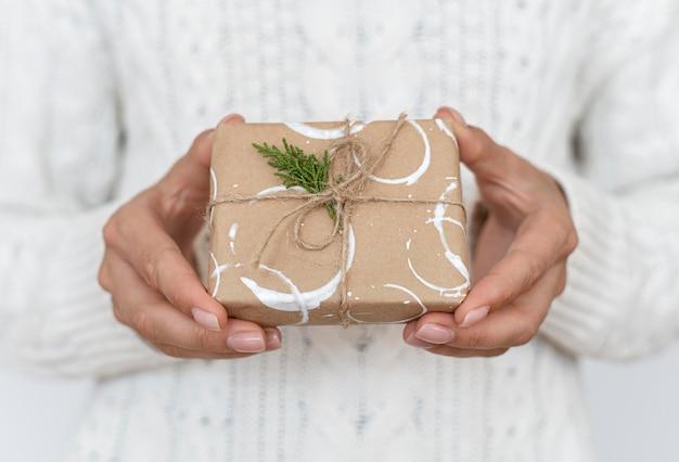 Вид спереди человека, держащего украшенный рождественский подарок