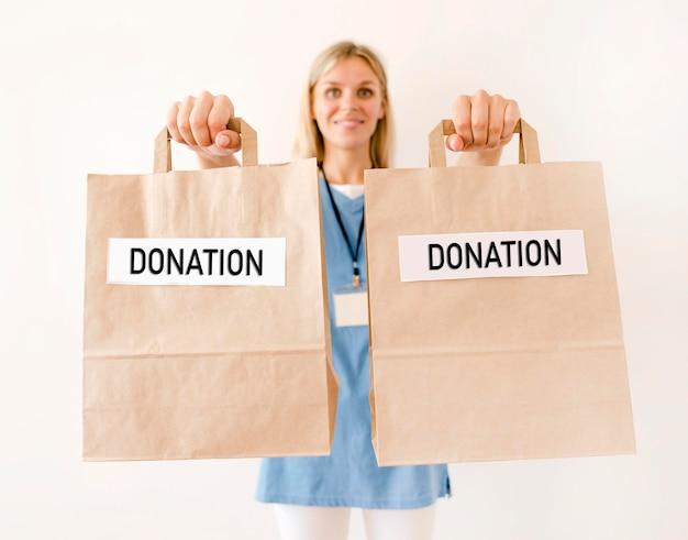 Вид спереди человека, держащего сумки для пожертвований