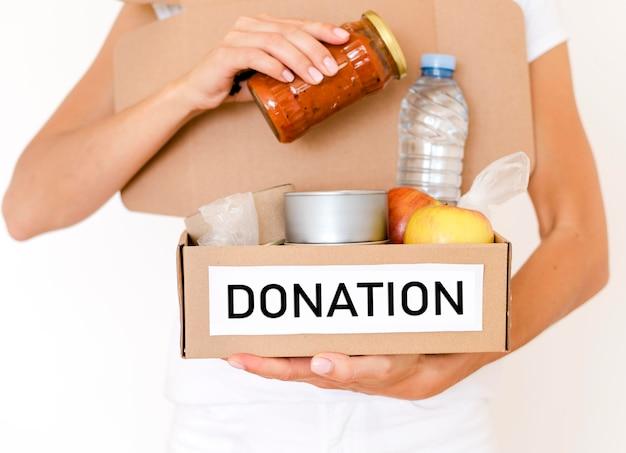 Вид спереди человека, держащего ящик для пожертвований